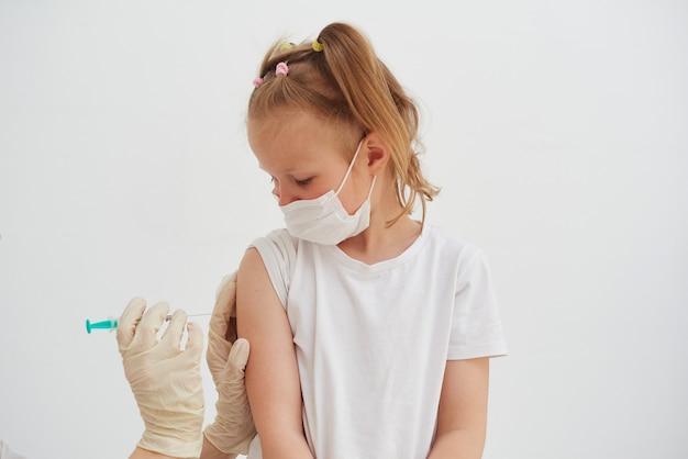 診療所での少女の予防接種。ウイルス対策の概念。