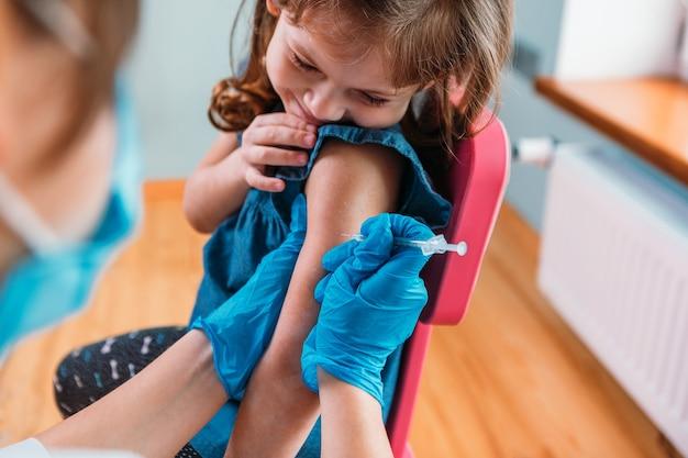 子供の予防接種。病院で子供を診察する医師。 covid-19