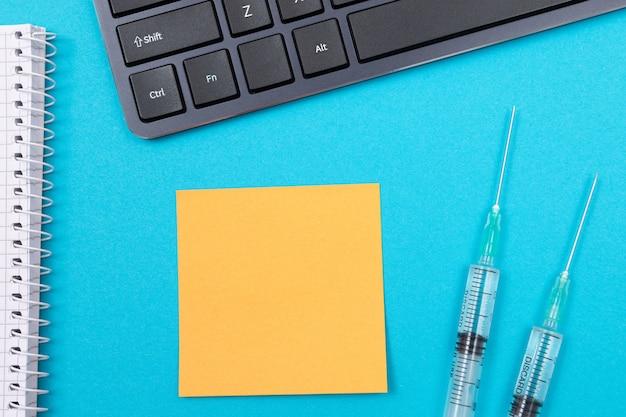 青いテーブルの上の予防接種または再ワクチン接種の概念2つの医療用注射器