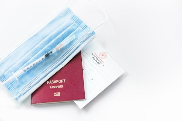 예방 접종 기록 카드, 터키 여권 및 의료 마스크가 테이블에 있습니다. 여행 개념에 대한 면역 여권 또는 증명서.
