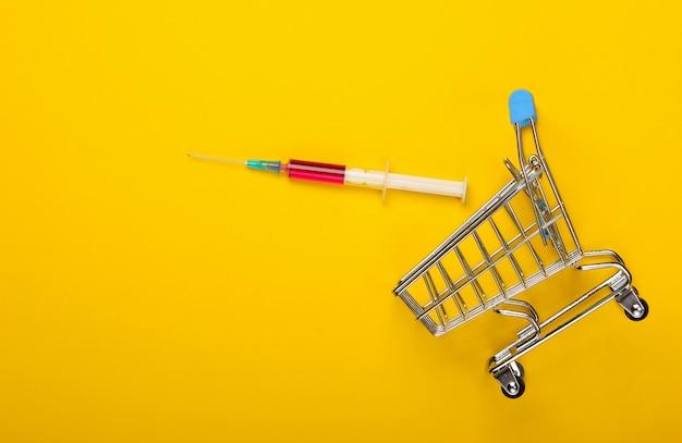 予防接種。黄色の背景に注射器とスーパーマーケットのトロリー。上面図