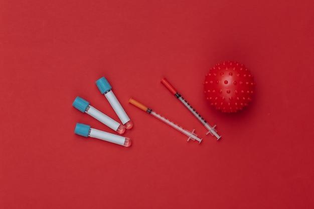 백신 접종. 주사기가 있는 테스트 튜브, 빨간색 배경에 바이러스 변형 모델. 평면도
