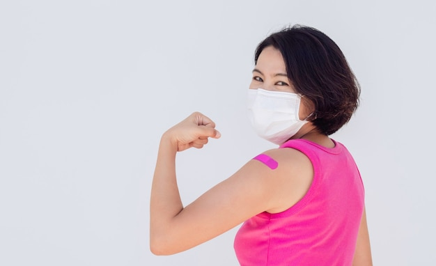 予防接種、予防接種を受けた人々のバナーの概念の包帯。コピースペースのある白のワクチン接種治療後、拳の手で強いジェスチャーを示す包帯石膏のマスクを身に着けているアジアの女性。