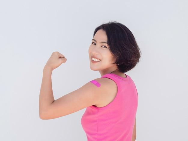 予防接種、予防接種を受けた人々の腕の概念の包帯。ピンクの包帯とワクチン接種後の笑顔で強いジェスチャーを示すピンクのタンクトップを着ている美しい魅力的なアジアの女性。