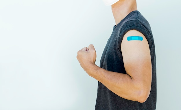 Vaccinations, bandage plaster and vaccinated people concept. blue bandage on strong man's arm who fist hand and showing muscle after vaccination treatment isolated on white background with copy space.