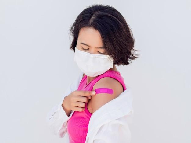 予防接種の概念。フェイスマスク、ピンクのノースリーブと白いシャツを着て、白で隔離されたワクチン接種治療後に彼女の肩にピンクの包帯石膏を見ているワクチン接種されたアジアの女性。