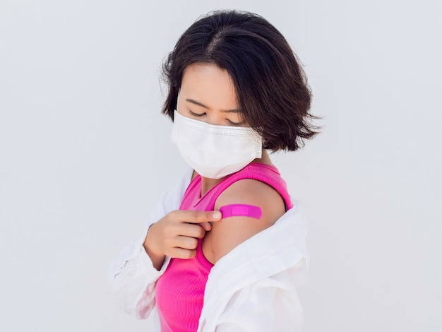 Vaccinations concept. vaccinated asian woman wearing a face mask, pink sleeveless and white shirt looking at pink bandage plaster on her shoulder after vaccination treatment isolated on white.