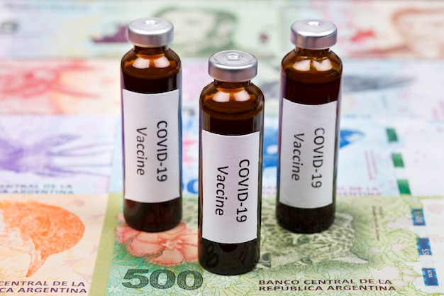 Vaccine against covid-19 on the background of argentinian pesos Premium Photo