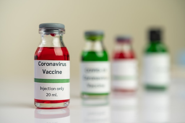 The vaccine against the covid-19 is in red and green in bottles placed on the floor.
