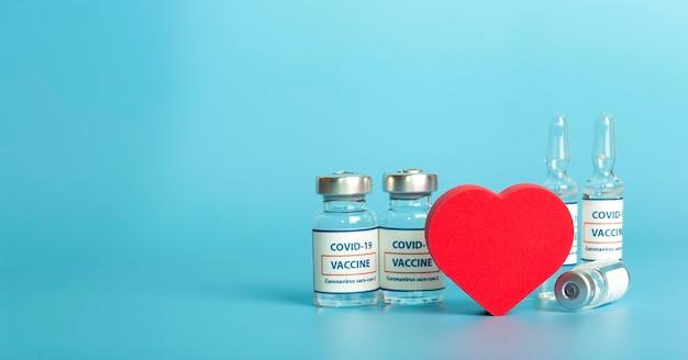 Вакцина против covid стеклянные медицинские флаконы с жидкой ампулой с вакциной против коронавируса и сердцем на ...