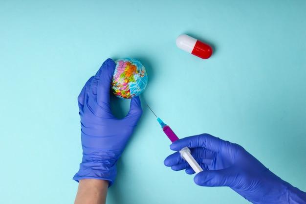 코로나 바이러스 (covid-19)의 세계적인 유행병에 대한 백신. 라텍스 장갑에 메딕 손을 잡고 파란색 배경에 지구본과 백신 주사기.