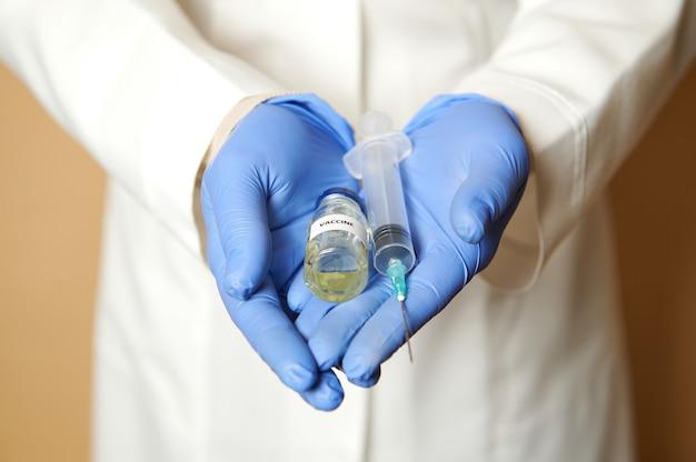 薬の手でワクチンと注射器