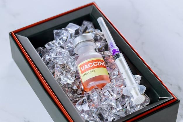 Covid-19、コロナウイルスsars-cov-2のワクチンを冷たく保つ氷上のワクチンボトルバイアルと注射器