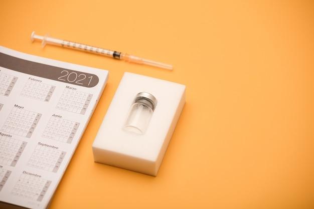 Флакон с вакциной, с календарем на 2021 год и шприц, серый фон