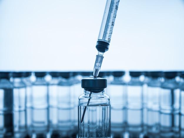 ワクチンボトルと注射器注射。アンプルの薬。実験室での液体サンプル用のガラスバイアル。