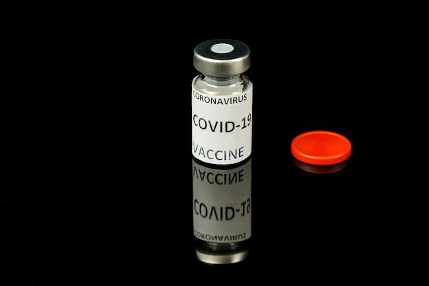 ワクチンの概念。銀と赤のキャップと黒い光沢のある背景の背景にコロナウイルスコビッド19ワクチンに署名した小さなガラス瓶。閉じる。セレクティブフォーカス。コピースペース
