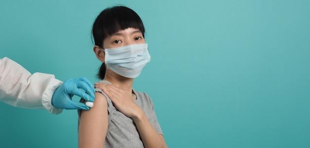 백신 개념. 의사가 코로나 바이러스 백신 주사를 기다리는 여자. 파란색 녹색 배경에 의료 마스크 오픈 어깨와 팔뚝 아시아 여자. 예방 접종을 기다리고 있습니다.
