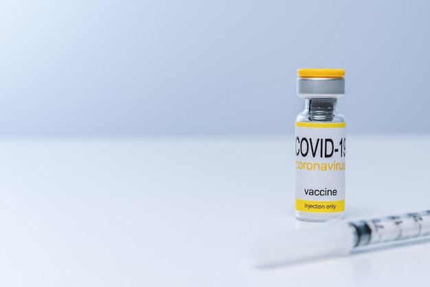 テーブルの上の注射器とガラスバイアルのワクチン