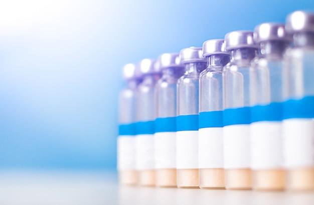 Бутылки для инъекций вакцины с белой этикеткой в ряд и копией пространства.