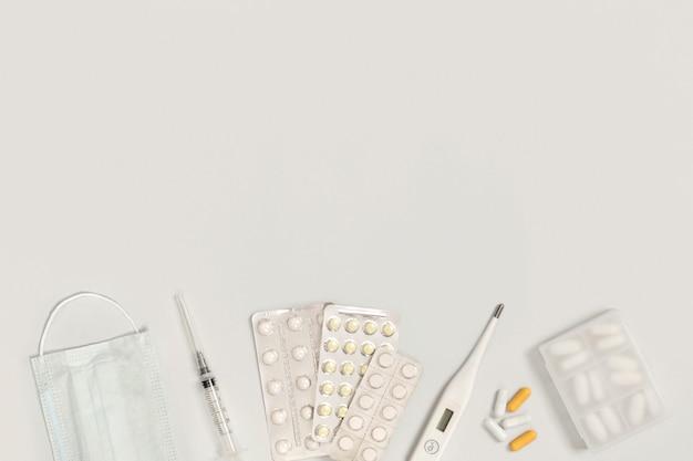 Вакцина, защитная медицинская маска, таблетки, шприц, термометр, держатель для планшета на белом фоне с пространством для текста. лечение простуды и гриппа.