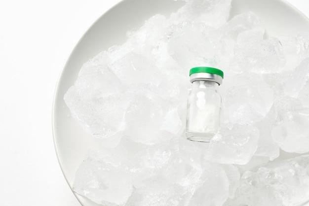 Холодильник для хранения вакцин. флаконы на льду. долгосрочное хранение вакцины covid-19. флаконы с вакциной против коронавируса хранятся при экстремальных температурах хранения.