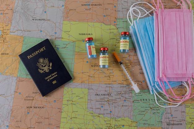 ワクチンバイアルボトルcovid-19米国の地図上の米国のパスポートでのコロナウイルスの発生中に旅行するためのワクチン感染予防予防接種を備えた旅行フェイスマスク