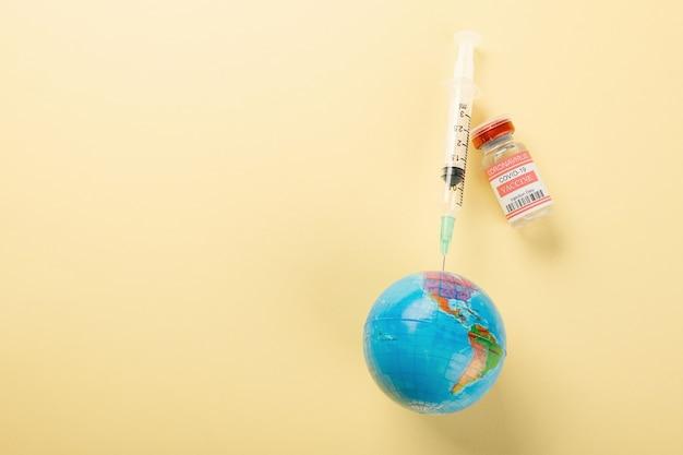 ワクチンバイアルは、コロナウイルスと地球に対するワクチン接種のための注射器を瓶詰めします