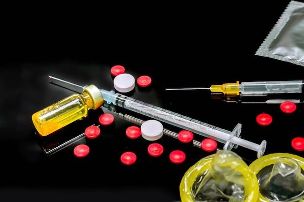 플라스틱 주사기와 콘돔이 있는 바이알, 흰색, 빨간색 의약품에 든 백신은 검정색 배경에 격리됩니다. hiv 감염의 원인 샘플. 그리고 콘돔은 감염을 예방하기 위한 것입니다.