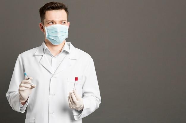 注射器とコピースペースを持つvacutainersを保持している医者の正面図