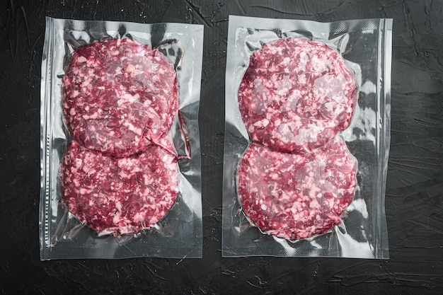 Vacuum beef cutlet sealed airtight pack set, on black stone table, top view flat lay
