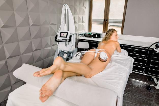 전문 장비로 슬리밍하는 허벅지와 엉덩이를위한 진공 바디 마사지. 뷰티 살롱에서 안티 셀룰 라이트와 지방 치료를 받고 젊은 예쁜 여자