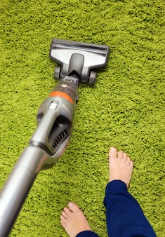 Vacuum cleaner in action - a men cleaner a carpet