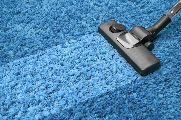 Vacuum cleaner on the blue carpet
