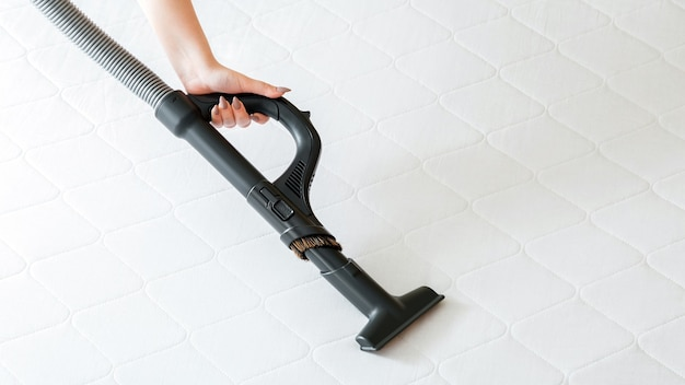 Vacuum cleaner machine in female hand do disinfection surfaces, cleanliness in hotel apartment. woman do professional cleaning mattress by vacuum cleaner from dust bacteria dirty. long web banner.