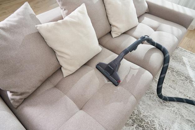 Пылесос на диване в пустой гостиной в современной квартире