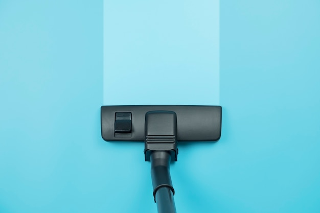 파란색 바닥 배경에 진공 청소기입니다.