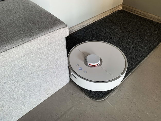 Vacuum cleaner robot runs on floor in a living room.