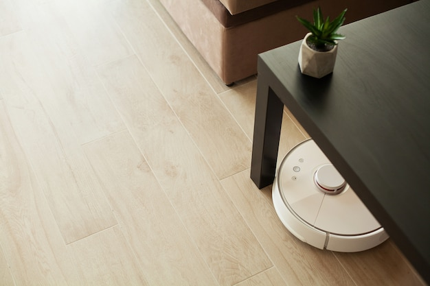 Vacuum cleaner robot runs on wood floor in a living room.