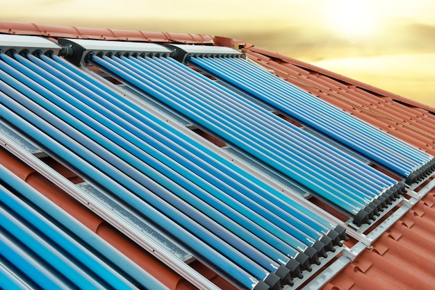 輝く太陽の下で家の赤い屋根にある真空コレクター太陽熱温水暖房システム