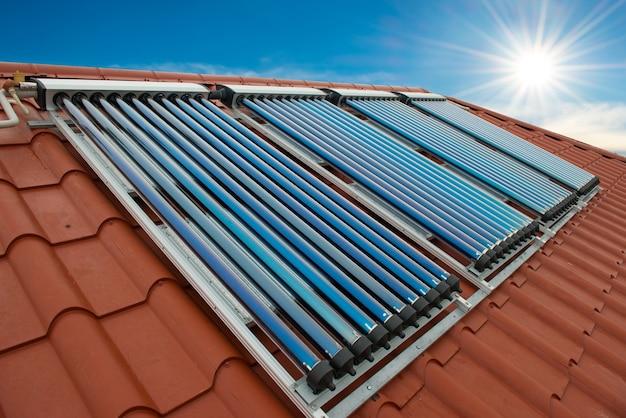 Вакуумные коллекторы - солнечная система водяного отопления на красной крыше дома.