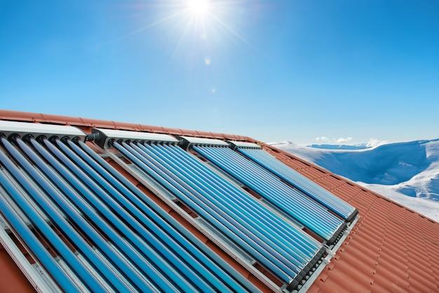 Вакуумные коллекторы - солнечные водонагревательные трубы на крыше дома с солнцем и снежными горами.