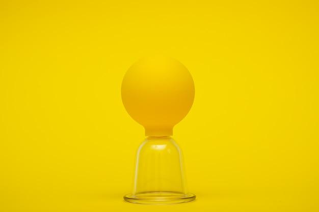 黄色の背景にセルライトに対するマッサージのための真空瓶