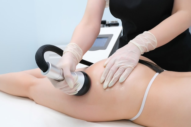 Vacuum massage device. vacuum massage of the buttocks and legs. anti cellulite body correction treatment. loss weight apparatus. young woman and doctor at medicine salon.