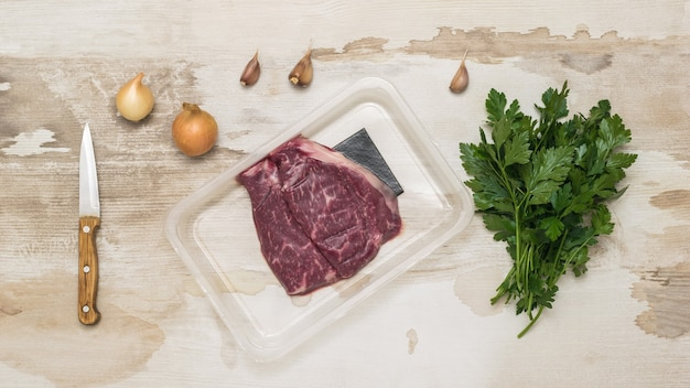 Vacuum-packed beef, knife and seasonings on a wooden table. sealed packaging for meat.