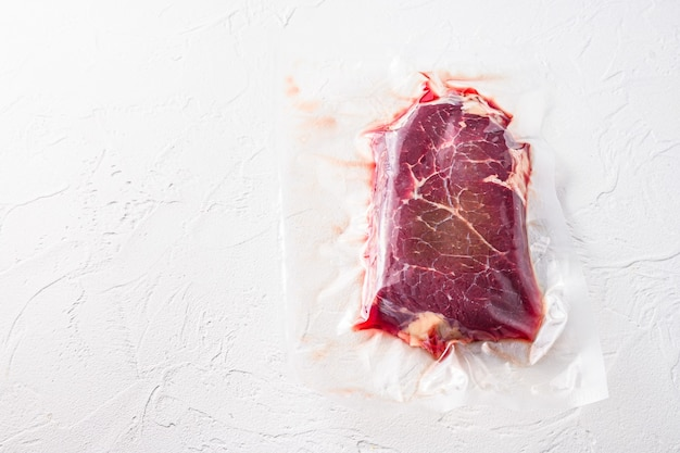 Vacuum packed organic beef meat   rump steak on white concrete  textured table, top view