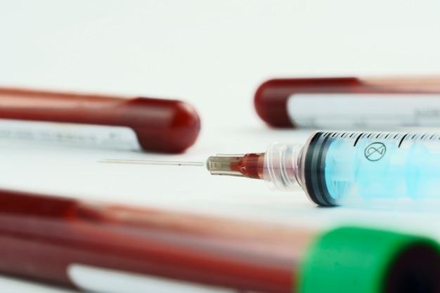 흰색 바탕에 수집 및 혈액 샘플을 위한 진공관. 보라색과 녹색 캡과 주사기로 투명합니다. 데이터를 식별하기 위한 레이블입니다. 선택적 초점입니다.