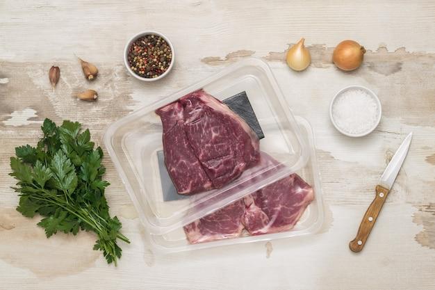 木製のテーブルに真空包装されたビーフステーキ、ナイフ、スパイス。肉用の密封包装。