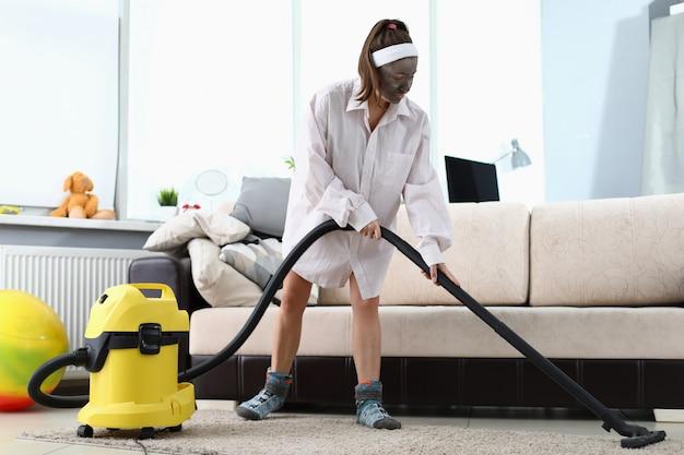 Молодая женщина в маске курорта красоты используя уборщика vacuun против домашней предпосылки. концепция образа жизни