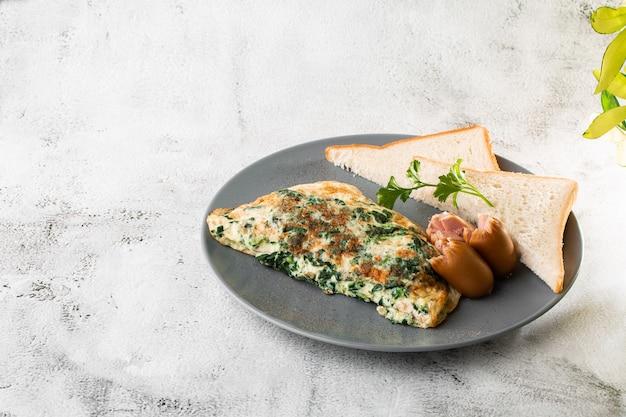 白い大理石の背景に分離されたvagetable、ほうれん草、ソーセージ、サワー種のトーストとオムレツ。手作りの料理。おいしい朝食。セレクティブフォーカス。 hotizontalの写真。