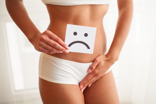 질 또는 비뇨기 감염 및 문제 개념. 젊은 여자는 조개 위에 sos와 종이 보유